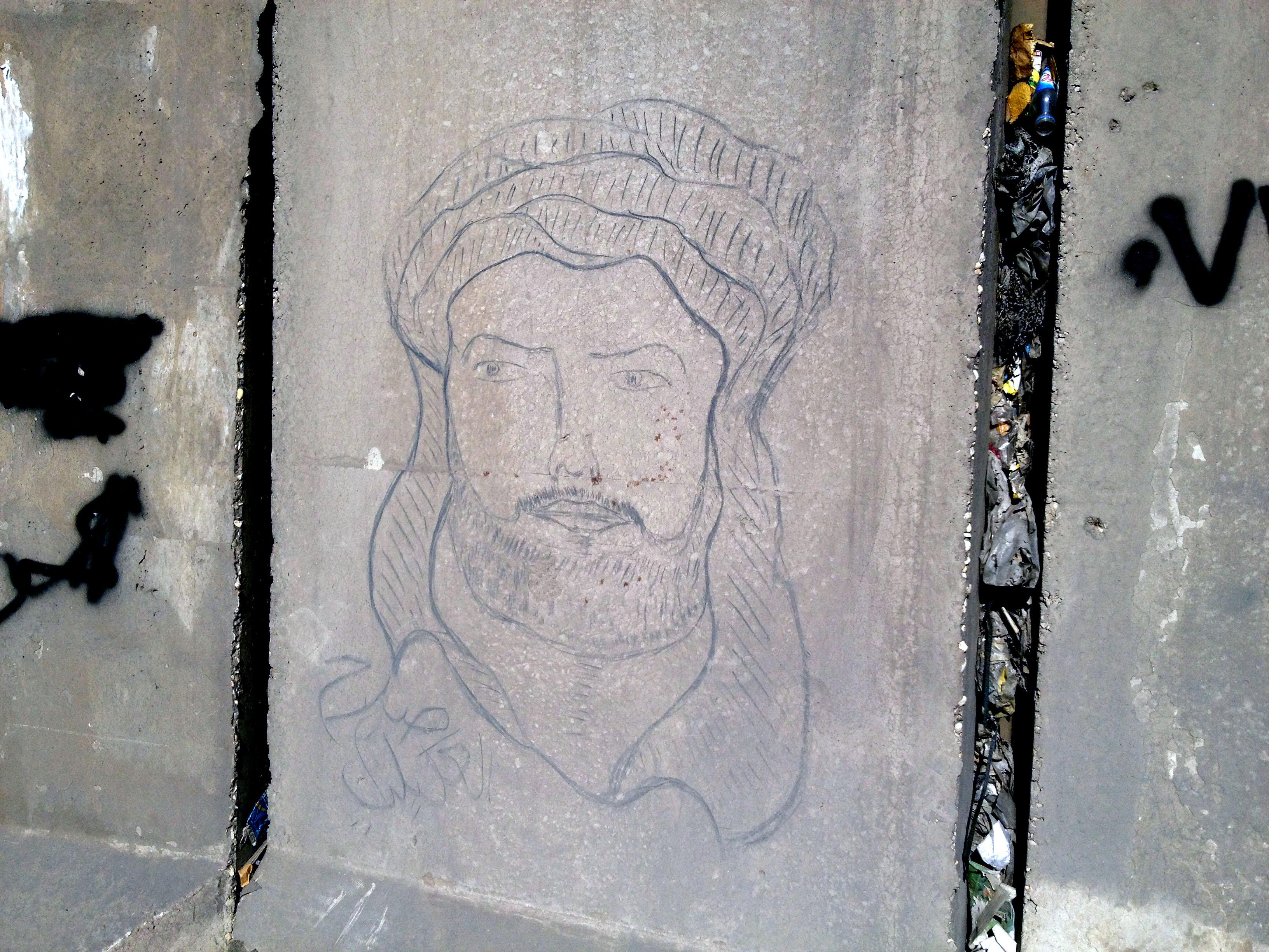 Desenho de Hussein, neto do profeta Maomé, em barreira de concreto de Bagdá. Crédito Diogo Bercito/Folhapress
