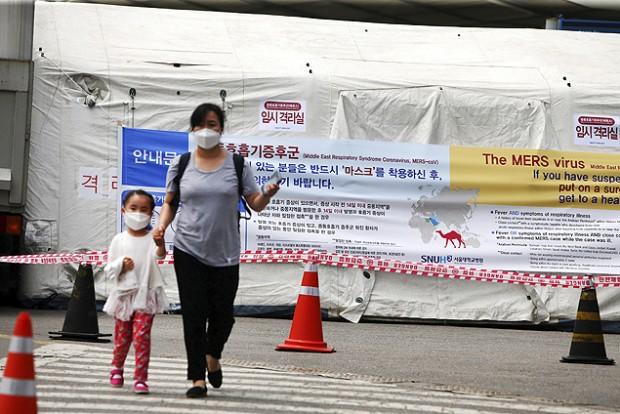Mulher leva criança pela mão em Seul utilizando máscara. Crédito Yang Ji-Woong - 2.jun.2015/Efe