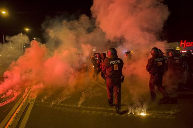 Policiais reagem a protestos contra imigrantes em Heidenau, no sábado (22). Crédito Axel Schmidt/Reuters