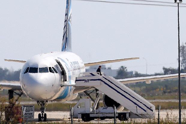 Um homem não identificado deixa o avião MS181, que foi sequestrado nesta terça-feira (29). Crédito Petros Karadjias-29.mar.16/Associated Press