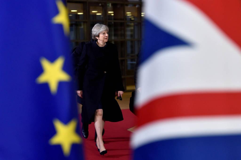 A primeira-ministra britânica, Theresa May, é vista entre bandeiras do Reino Unido e da União Europeia em cúpula em Bruxelas, em dezembro de 2017
