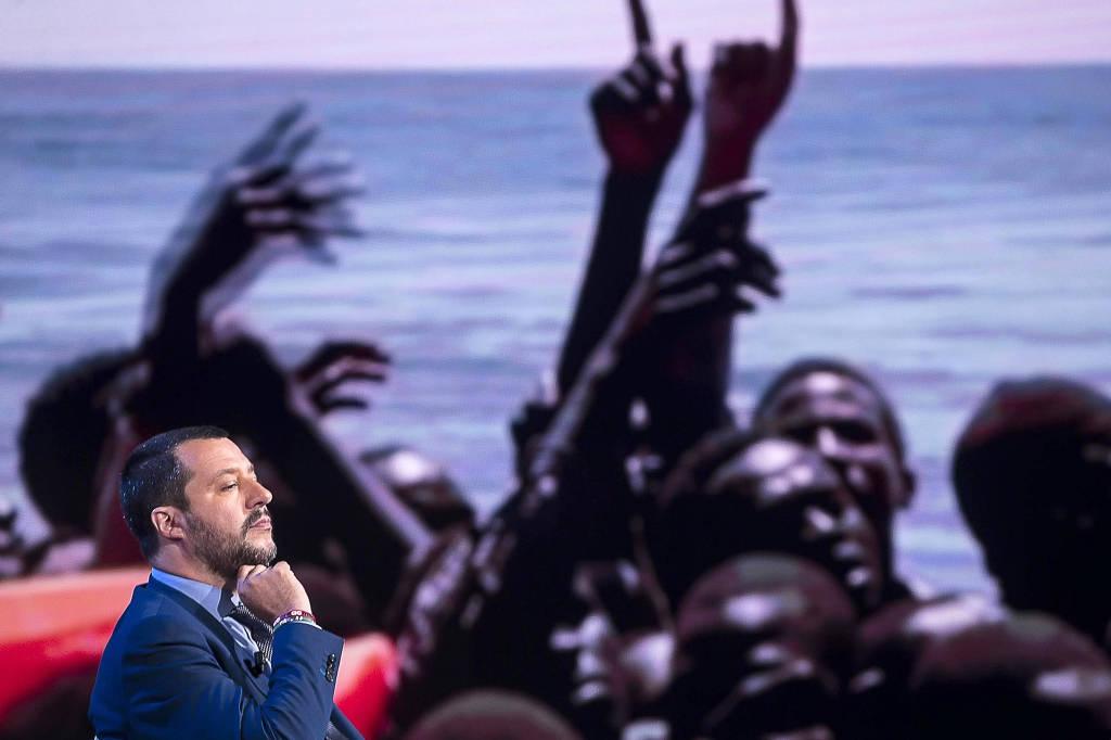 Matteo Salvini, ministro do Interior italiano, discursa em frente a painel com foto de imigrantes africanos em barco no Mediterrâneo